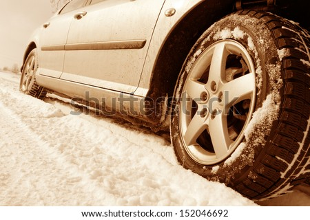 Close up of a cars tires on a snowy road - sepia tone - stock photo