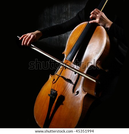 Close up of a cello musician on dark background - stock photo