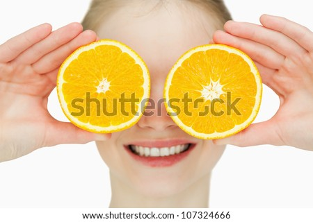 Close up of a cheerful woman placing oranges on her eyes against white background