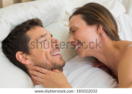 Close-up of a cheerful young couple lying together in bed at home - stock photo