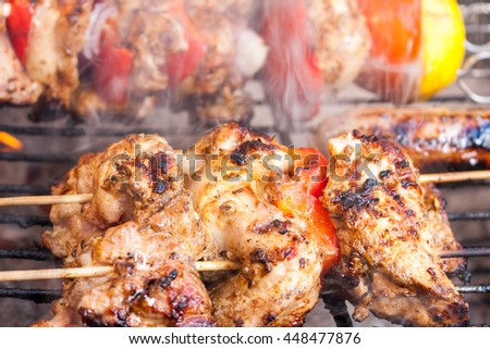 Close-up of a chicken shawarma kebab skewer gently cooking on a smoking barbecue