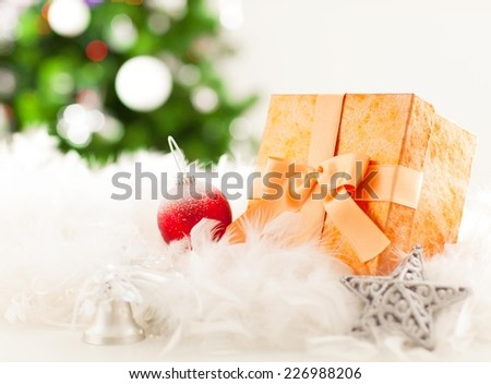 Close up of a Christmas tree decoration and gift box - christmas tree in the background.