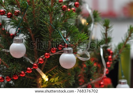 close up of a christmas tree with red beds and white ball ornaments