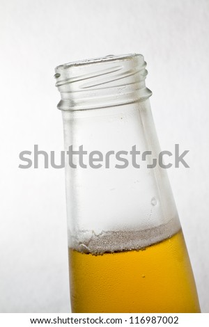 Close up of a clear glass beer bottle.
