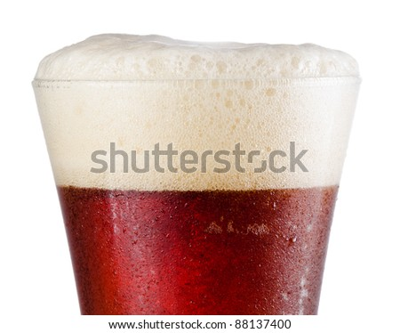Close up of a cold beer in pilsner style glass with half beer and half head above rim