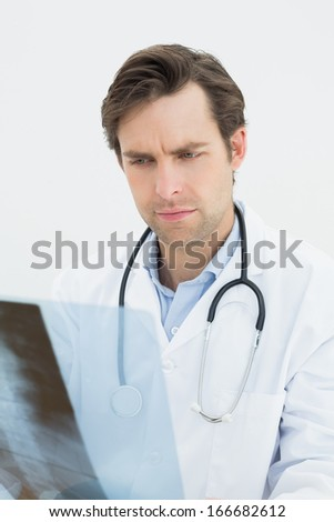 Close-up of a concentrated male doctor examining spine x-ray over white background