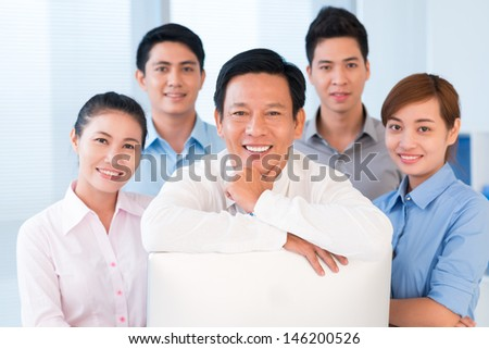 Close-up of a confident business team smiling and looking at camera - stock photo