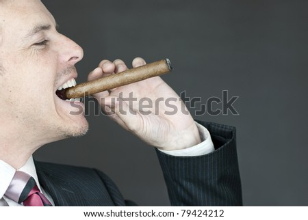 Close-up of a confident businessman celebrating with a cigar. - stock photo