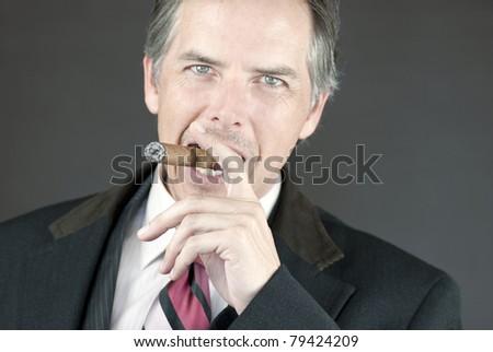 Close-up of a confident businessman smoking a cigar. - stock photo