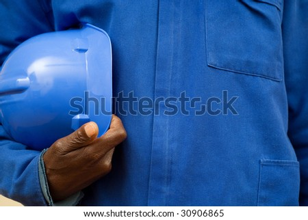 Close up of a construction worker holding hard hat under his arm - stock photo