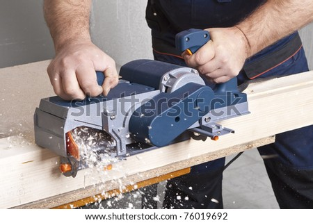 Close-up of a construction worker's hand and power tool while planing a piece of wood trim for a project.
