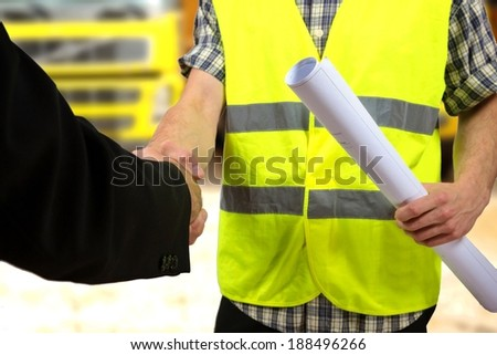 Close up of a construction worker's hand holding project documents and shaking hands. - stock photo