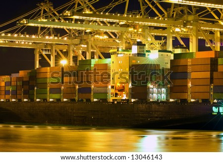 Close up of a container ship being unloaded - stock photo