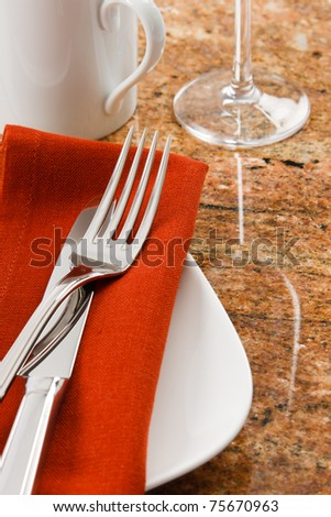 Close up of a contemporary table setting showing silverware, mug and wine goblet with copy space