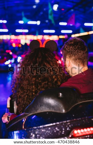 Close up of a couple in a bumper car, amusement park. Selective focus, intentional motion blur and color shift