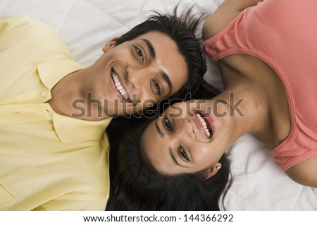 Close-up of a couple lying on the bed and smiling - stock photo