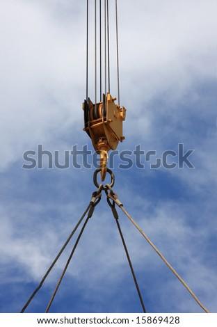 Close up of a crane hook lifting something - stock photo