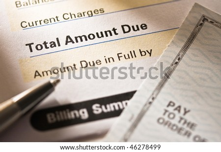 Close up of a credit card statement with personal check on top. - stock photo