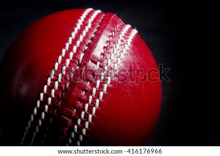 Close up of a cricket ball seam with black background - stock photo
