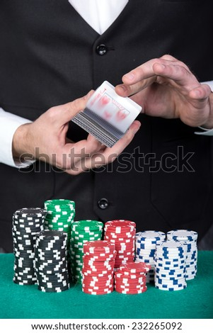 Close-up of a croupier is holding playing cards, gambling chips on table.