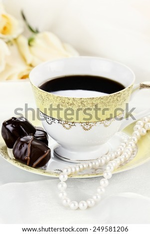Close up of a cup of coffee chocolate candies and pearl necklace. Roses in the background. Shallow depth of field. - stock photo