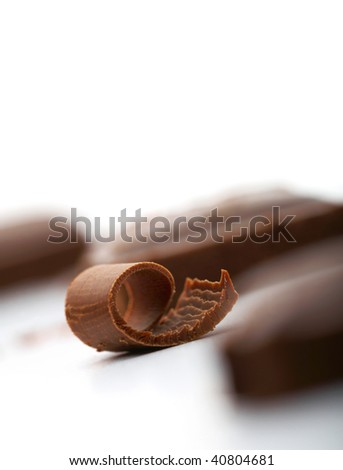Close-up of a curl of chocolate on white with a piece of chocolate at the background
