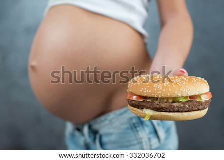 Close up of a cute pregnant belly and junk food. Hamburger and pregnancy. Pregnant female unhealthy motherhood concept. Side view, pregnant belly body part