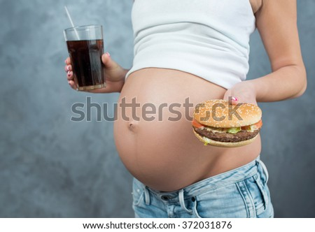 Close up of a cute pregnant belly tummy and junk food. Hamburger and pregnancy. Pregnant female unhealthy and healthy motherhood concept. Side view, pregnant belly body part. Third trimester - stock photo
