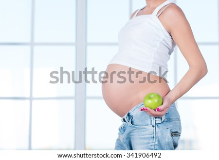 Close up of a cute pregnant belly tummy belly and healthy food. Pregnant female healthy motherhood concept. Side view, pregnant belly body part. New life third trimester - stock photo