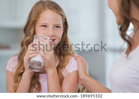 Close-up of a cute smiling girl drinking milk as she looks to her mother in the house - stock photo