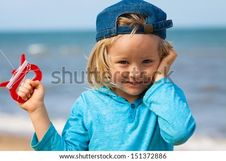 Close-up of a cute young boy flying a kite at the beach. - stock photo
