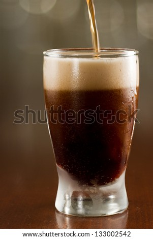 close up of a dark beer on a busy bar top - stock photo