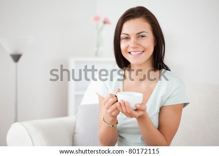 Close up of a dark-haired woman drinking tea in her living room