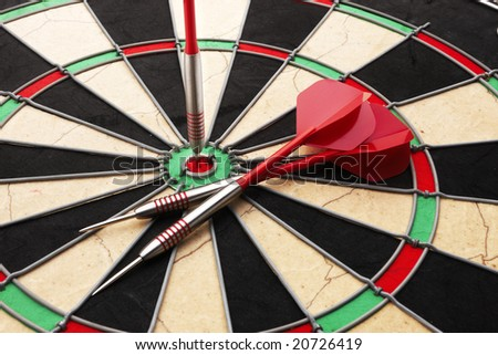 Close up of a dartboard and darts with a bulls-eye