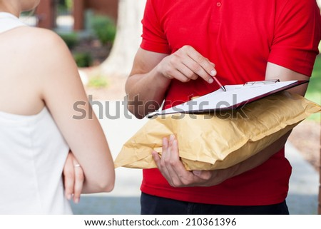 Close-up of a delivery man asking for a signature - stock photo