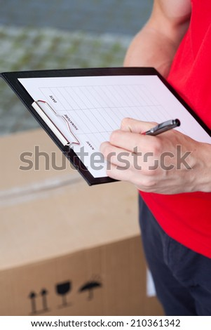 Close-up of a delivery man filling in transport document - stock photo