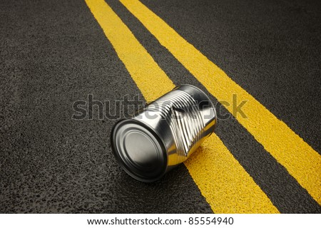 Close up of a dented, shiny, metal can sitting on an black asphalt road with yellow stripes