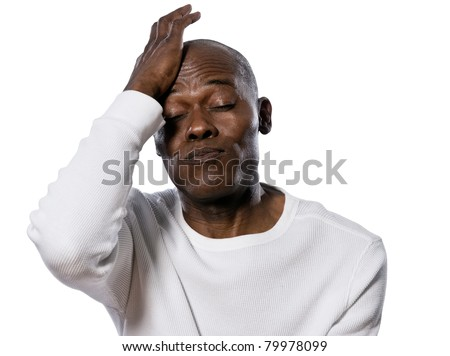 Close-up of a displeased afro American man with hand on head puffing in studio on white isolated background - stock photo