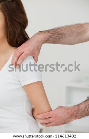 Close-up of a doctor examining the shoulder of a patient in a room - stock photo