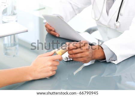 Close up of a doctor giving drugs to his patient during an appointment in his office - stock photo