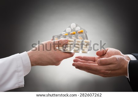 Close-up Of A Doctor's Hand Giving Various Medicines To Patient - stock photo