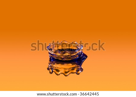 close up of a drop of water on orange backdrop