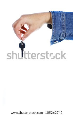 Close-up of a female hand holding a key between her forefinger and thumb - isolated on white - stock photo