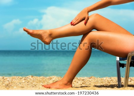 Close up of a female legs at the beach. - stock photo
