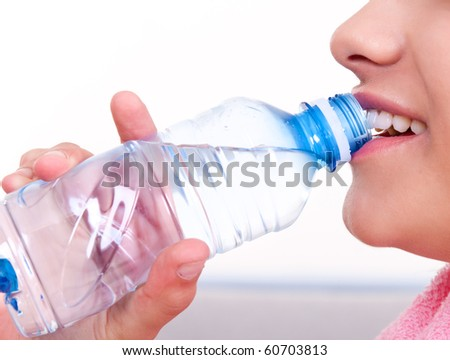 close-up of a female mouth drinking water from a bottle - stock photo