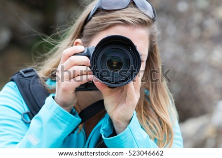 Close up of a female photographer taking picture
