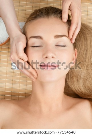 Close-up of a female receiving facial massage at spa salon - stock photo