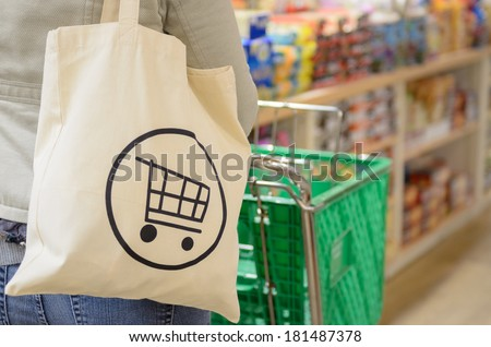 Close up of a female shopper with a canvas tote bag pushing a shopping cart down the isle of a specialty grocery store.