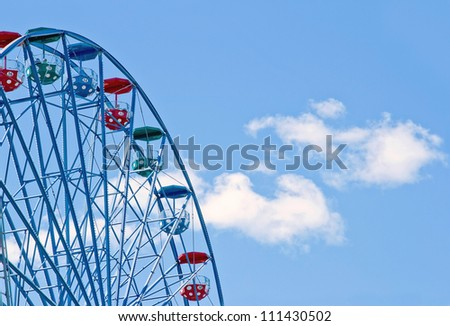 Close-up of a ferris wheel on a sunny day with blue sky and clouds - stock photo