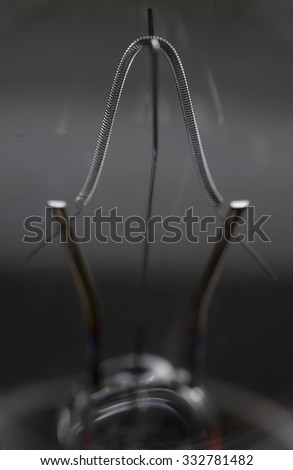 Close-up of a filament in a incandescent light bulb with shallow depth of field - stock photo